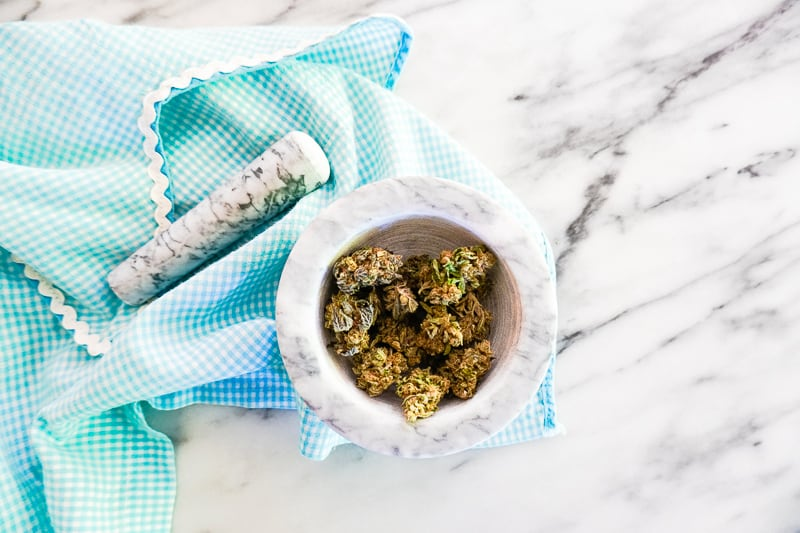 dried buds with a handheld grinder