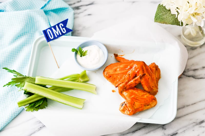 Chicken Wings with ranch dressing and celery sticks and OMG sign