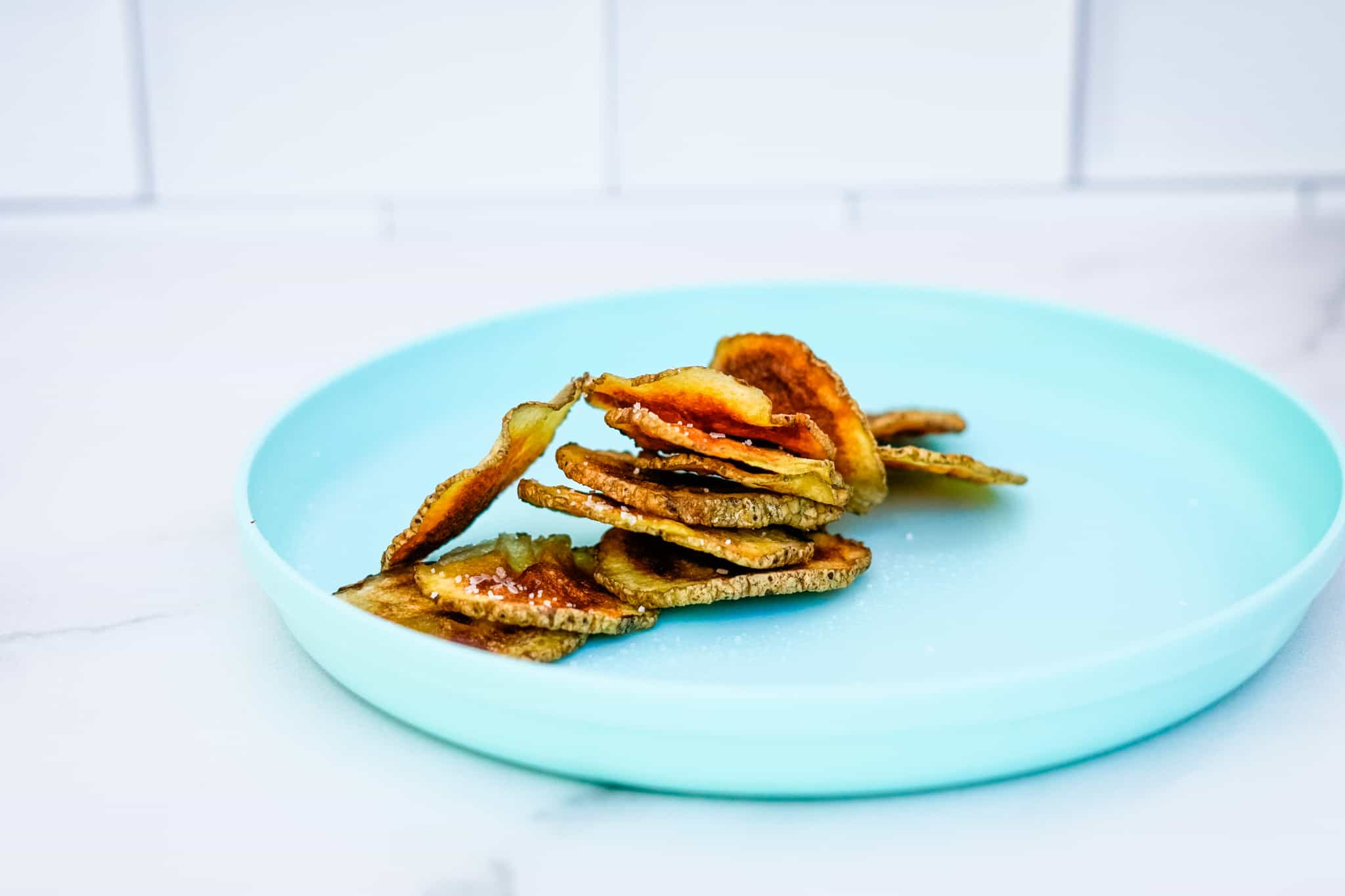Crispy, crunchy cannabis potato chips on a turquoise plate. Made in the microwave.